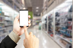 Hand holding smart phone with blur background of shopping mall m Stock Image