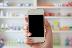 Hand holding smart phone with blur some shelves of drug. Pharmacist hand holding smart phone with blur some shelves of drug in the pharmacy drugstore Royalty Free Stock Photography