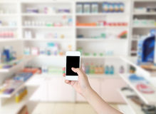 Hand holding smart phone with blur some shelves. Of drug in the pharmacy Stock Photos