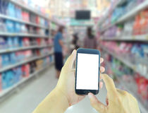 Hand holding smart phone with blur supermarket background Stock Photography