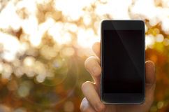 Hand holding smart phone, blurred background Stock Photo
