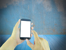 Hand holding smart phone with blurred grunge background Stock Photos
