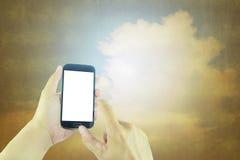 Hand holding smart phone on blurred vintage background Stock Image