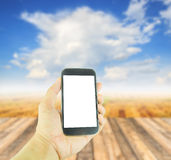 Hand holding smart phone on blurred wooden table background Stock Images