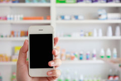 Hand holding smart phone with blurshelves of drug. Closeup pharmacist hand holding smart phone with blur some shelves of drug in the pharmacy drugstore Royalty Free Stock Photo