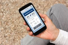 Hand holding smart phone with boarding pass concept on screen. All screen content is designed by me stock image