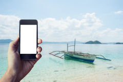 Hand holding smart-phone with Boats waiting for tourists to travel between the islands background Royalty Free Stock Image