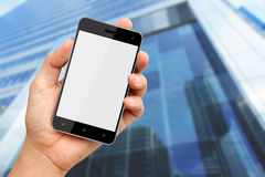 Hand holding smart phone with building background Stock Images