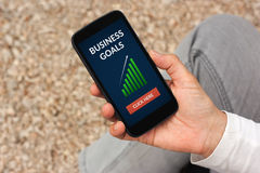 Hand holding smart phone with business goals concept on screen Royalty Free Stock Images
