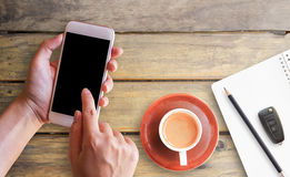 Hand holding smart phone and cup of coffee royalty free stock photography