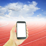 Hand holding smart phone at curve of a running track Stock Image