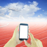 Hand holding smart phone at curve of a running track Stock Photos