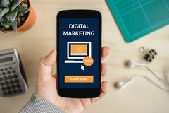 Hand holding smart phone with digital marketing concept on screen. Flat lay royalty free stock photography