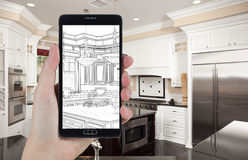 Hand Holding Smart Phone Displaying Drawing of Kitchen Photo Behind stock images