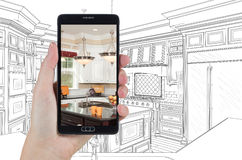 Hand Holding Smart Phone Displaying Photo of Kitchen Drawing Beh Stock Photography