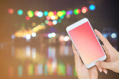 Hand holding smart phone with empty screen on street evening lig Royalty Free Stock Photo