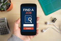 Hand holding smart phone with find a job concept on screen Stock Photo