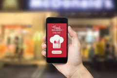 Hand holding smart phone with food delivery order screen. Hand holding smart phone with food delivery order screen on blur of restaurant background Stock Image