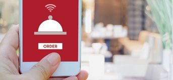 Hand holding smart phone with food online device on screen over. Blur restaurant background, banner wuth copy space, food online, food delivery concept Royalty Free Stock Photography