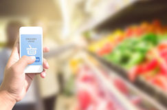 Hand holding smart phone with grocery shopping online on screen. Over blur supermarket background, retail business and technology concept Royalty Free Stock Photography