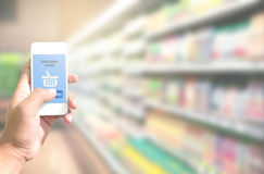 Hand holding smart phone with grocery shopping online on screen. Over blur supermarket background, retail business and technology concept Royalty Free Stock Images