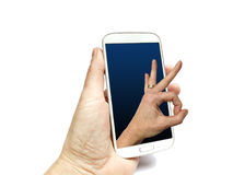 Hand holding smart phone with hand making international ok sign. Coming out of screen Royalty Free Stock Photos