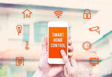 Hand holding smart phone with home control application with blur Stock Image