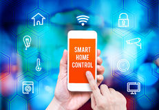 Hand holding smart phone with home control application with blur Royalty Free Stock Photo