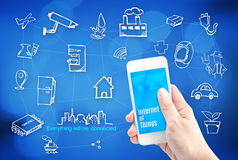 Hand holding smart phone with Internet of things (IoT) word and Stock Photo