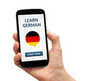 Hand holding smart phone with learn german concept on screen Royalty Free Stock Photo