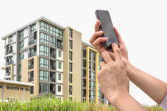 Hand holding a smart phone and new condominium. Stock Photos