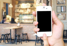 Hand holding smart phone over blur restaurant background Stock Images