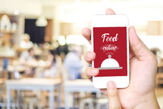 Hand holding smart phone over blur restaurant background Royalty Free Stock Photos