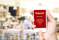 Hand holding smart phone over blur restaurant background Stock Image