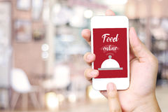 Hand holding smart phone over blur restaurant background Stock Photos