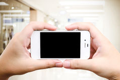 Hand holding smart phone over blur store background royalty free stock photo