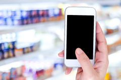 Hand holding smart phone over blur supermarket background. Retail business , shopping online and technology concept stock photos