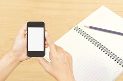 Hand holding smart phone over note book paper Royalty Free Stock Photo