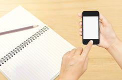 Hand holding smart phone over note book paper Royalty Free Stock Photography
