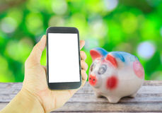 Hand holding smart phone on piggy bank on wooden table backgroun Stock Image