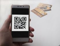 Hand holding smart phone with QR code. 3 bank cards on background. Man hand holding a phone with qr code on the screen. There are 3 bank cards on the background royalty free stock photos
