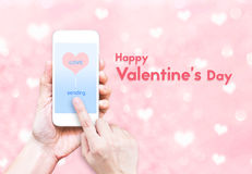 Hand holding smart phone with sending love word and heart shape Royalty Free Stock Photo