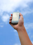 Hand holding smart phone in the sky. Outside shot of a hand holding smart phone in the sky Stock Image
