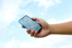 Hand holding smart phone on the sky background Stock Image