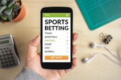 Hand holding smart phone with sports betting concept on screen