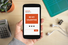 Hand holding smart phone with valentine`s day concept on screen Royalty Free Stock Image