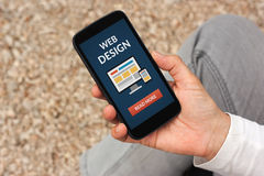 Hand holding smart phone with web design concept on screen Royalty Free Stock Photos