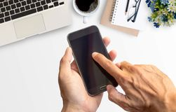 Hand holding smart phone with white minimal office desk table. With laptop computer,notebook,glasses,pencil,and cup of coffee. Top view with copy space for text Stock Image