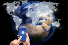 Hand holding smart phone on world map network and wireless commu Stock Image