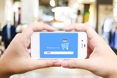 Hand holding smart phone with www. on search bar over blur store Stock Images